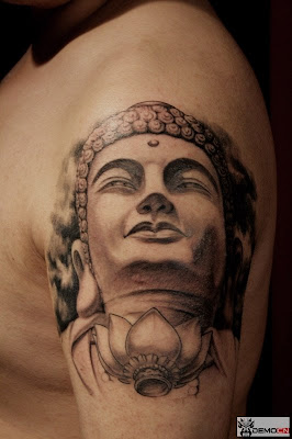 Buddha tattoo design on the arm with big ears and lotus.
