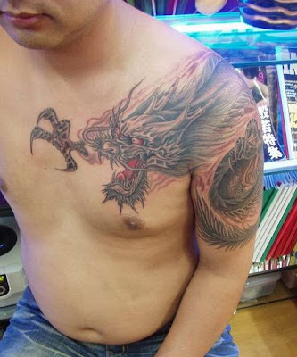fighting dragon tattoo on the shoulder and arm