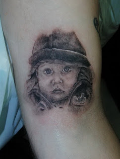 baby face portrait tattoo on the arm