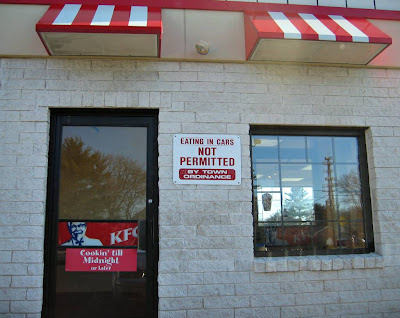 Sign on the outside of a KFC in Bloomfield, CT stating that eating in cars is not permitted by a town ordinance