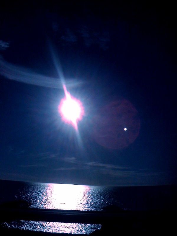 Amazing photo of sun and lighted objects over ocean at Carlsbad California