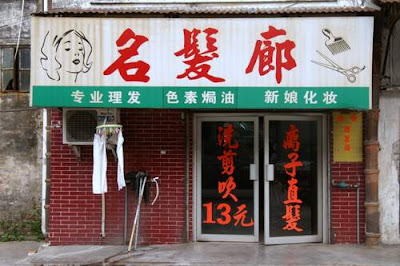 Image of the whole frontage of the hairstylist's shop in Kaifeng, Guangzhou Province, China. The characters in red read 'Ming Fa Lang' which translates, roughly, to 'Famous Hair Corridor' (Corridor as in the Long Corridor in the Summer Palace, outside of Beijing... if that makes things easier).