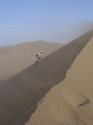 Image of your Scribe walking along a vast sand dune