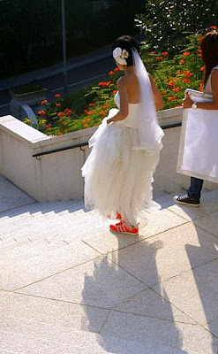 Picture of a bride lifting up her dress to show off her glowing orange shoes; or maybe to walk down the stairs without tripping or dirtying her hem