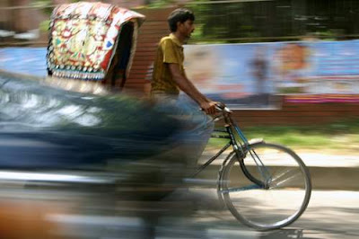 Image of a fast moving rickshaw cyclist in vehicular traffic