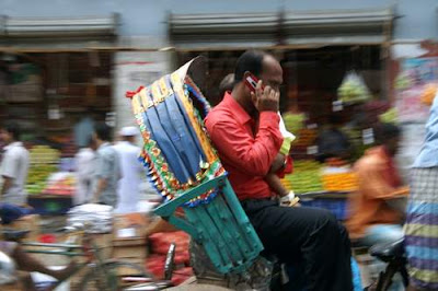 image of a rickshaw passenger talking on his cellular phone