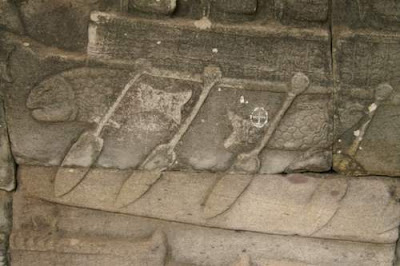 Bas-relief image of Khmer paddlers in a boat, close up on the paddles and the omnipresent fish in the Tonlé Sap