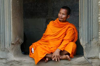Image of a Buddhist monk sitting under a lintel in Angkor Wat