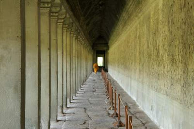 Image of a monk wandering down one of the corridors at the main temple of Angkor Wat