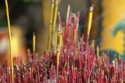 Close up image of incense burning and sweet, scented smoke wafting sideways and upwards.