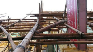 Image of bamboo scaffolding around a small building in Hong Kong from directly beside the bottom supports.