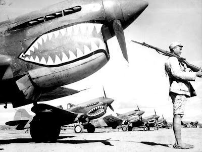 Image of a Chinese soldier guards a line of American P-40 fighter planes, painted with the shark-face emblem of the `Flying Tigers,' at a flying field somewhere in China. ca. 1942. Image was sourced from the Wikimedia Commons and is from the public domain because This image is now in the public domain because its term of copyright has expired in China. According to copyright laws of the People's Republic of China (with legal jurisdiction in the mainland only, excluding Hong Kong and Macao) and the Republic of China (currently with jurisdiction in Taiwan, the Pescadores, Quemoy, Matsu, etc.), all photographs enter the public domain fifty years after they were first published, and all non-photographic works enter the public domain fifty years after the death of the creator.