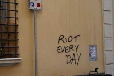 Graffiti image of the phrase 'riot every day' found on a peaceful street, above a parked Vespa, from the old town centre of Genoa, Italy.
