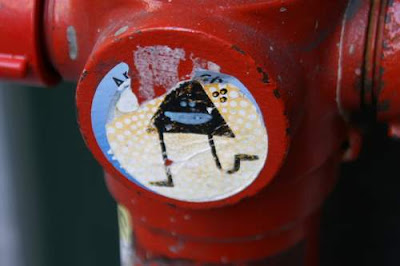 Graffiti image of a sticker graffiti of triangle man running, stuck onto a fire hydrant, from the old town centre of Genoa.