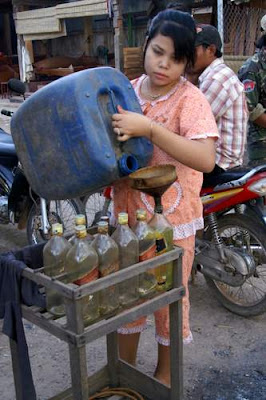Image of a roadside gas, or petrol, stand and station operator in Cambodia...
