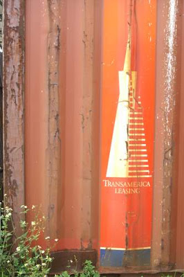 Image of a rusted container with a 'Transamerica Leasing' leasing logo on it.