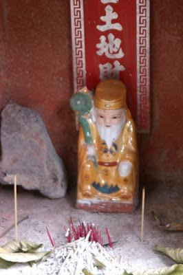 Image of a deity, and burnt incense, at a small, curbside shrine in Hong Kong.