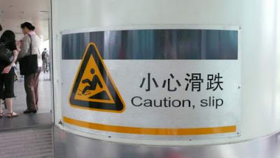 Image of a sign in Shenzhen airport reading 'Caution, slip'