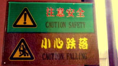 Image of a warning on the wall in the belfry in Dali, Yunnan Province, China. It reads 'Caution' with an image of an exclamation mark in a yellow warning triangle. Underneath it is an image of a person plunging, headfirst, through the air, with the slogan 'Caution, Falling'...