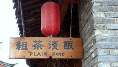 Image of a restaurant sign in Yunnan Province, China, advertising 'plain food' for spice-challenged foreigners... in front of a garland of drying chillis...