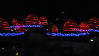 Image of many neon-lit 'Chinese Junks' on the water for the opening of the 2009 East Asian Games in Hong Kong