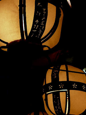 Image of metal and paper lanterns, by night, outside a temple in Kyoto, Japan.