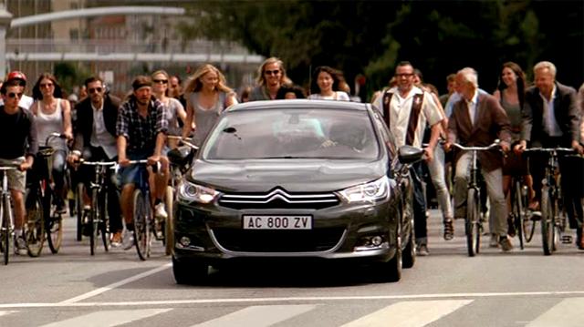 Un Citroën C4 rodeado de ciclistas