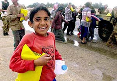 Chico irakí muestra ayuda humanitaria como si fuera un regalo dice....