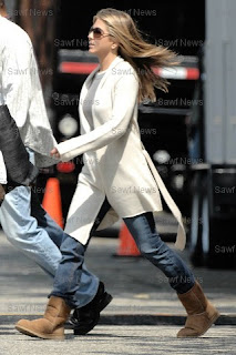 ... attired in a white cashmere wrap cardigan, sunglasses, jeans and chocolate classic short Ugg boots with her famous hair blowing in the wind.