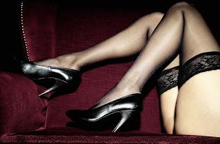 Longas pernas em salto alto e negras meias de ligas