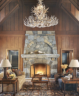 Wood paneled living room with vaulted ceiling, an antler chandelier and stone fireplace and mantel by Peter Pennoyer