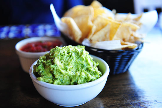 A generous portion of guacamole with salsa and chips