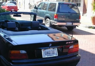 funny photo of blond licence plate hung back to front or upside down on a black bmw