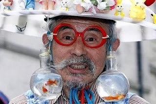 funny jokes photos man wearing stupid hat and goldfish bowls as earrings with big red glasses fancy dress