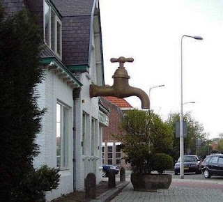 funny house photo with a really large water tap out the front