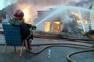 funny pic of fireman taking a rest sitting down in chair while fighting fire with hose