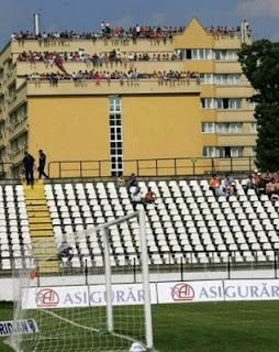 funny football photos soccer ground with empty stand all the spectators are in the building next door