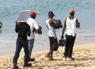 funny beahc photo 4 guys walking carrying stereo no batteries needed with solar panel