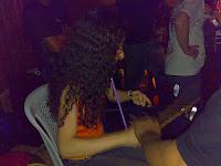 Sara tocando agogô, orientada por Ronaldo