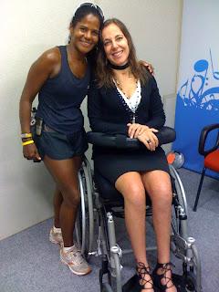Foto de corpo da atleta Pretinha, que está usando roupa de corrida (shorts e blusa regata), abraçada com a apresentadora Mara Gabrilli, que usa sai e blusa pretas. As duas sorriem para a fotografia.