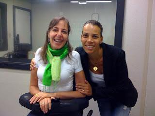 Foto de Mara Gabrilli, à esquerda, de cabelo meio preso, camiseta branca e lenço verde. Ao seu lado, Regina Moraes, de blazer azul, camiseta branca e cabelos presos. As duas estão sorrindo.