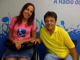 Mara sorrindo ao lado de Humberto Alexandre,vestido com uma camisa amarela e calça jeans, ele sorri ao lado da apresentadora