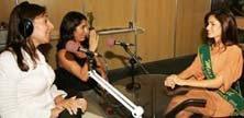 Mara de frente para Vanessa Vidal, miss surda que se comunica por intermédio de uma tradutora em libras, sentada ao lado de Mara no Estúdio móvel montado dentro da Feira Reatech