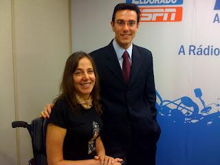 Foto de Mara sorrindo ao lado de João Maradei, que veste terno azul marinho,gravata bordô e óculos de armação clara. Eles estão no Estúdio da Rádio Eldorado
