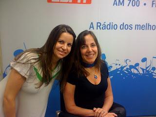 Silvana Bicudo sorrindo ao lado da apresentadora Mara Gabrilli. Silvana tem olhos e cabelos  longos claros. Ela veste uma blusa branca e verde