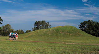 Visitors walk around one of the earthen mounds