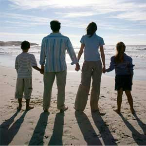 A family holding hands looking at the ocean.
