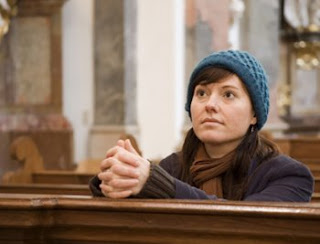 A woman praying in a church