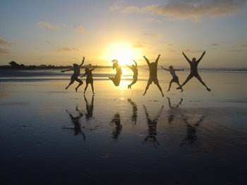 People dancing on a beach in front of the rising sun.