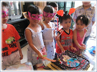 Twins cutting their birthday cake, with cousins joining in the fun